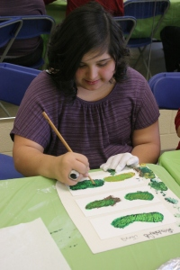 A participant paints flowy, green branches.